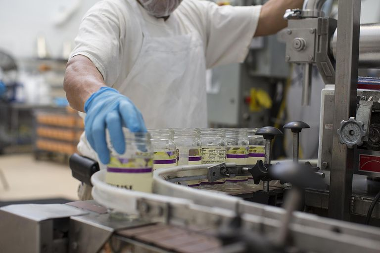 Man handling glass jars on production line