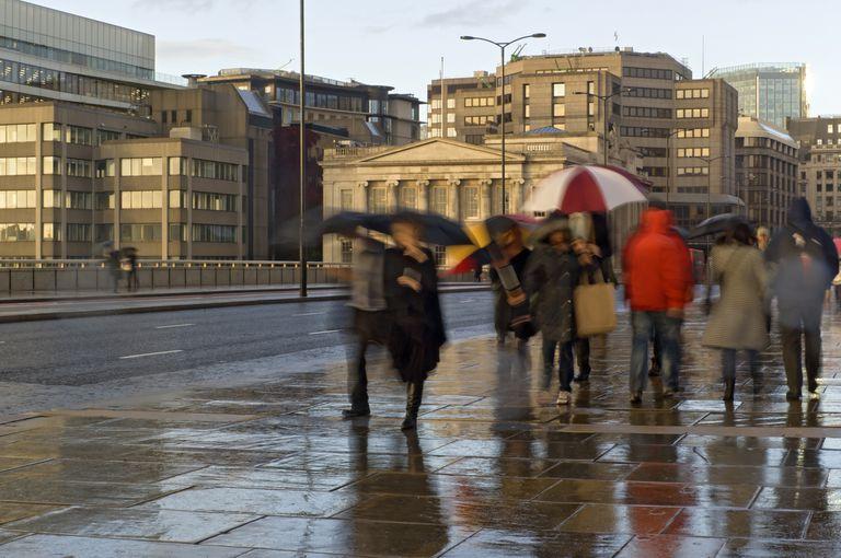 People walking on pavement in rain, London, UK