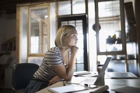 focused woman working at laptop in office
