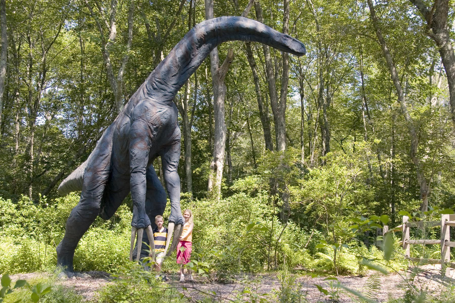Modle of Therizinosaurus outside with two children posing by hands