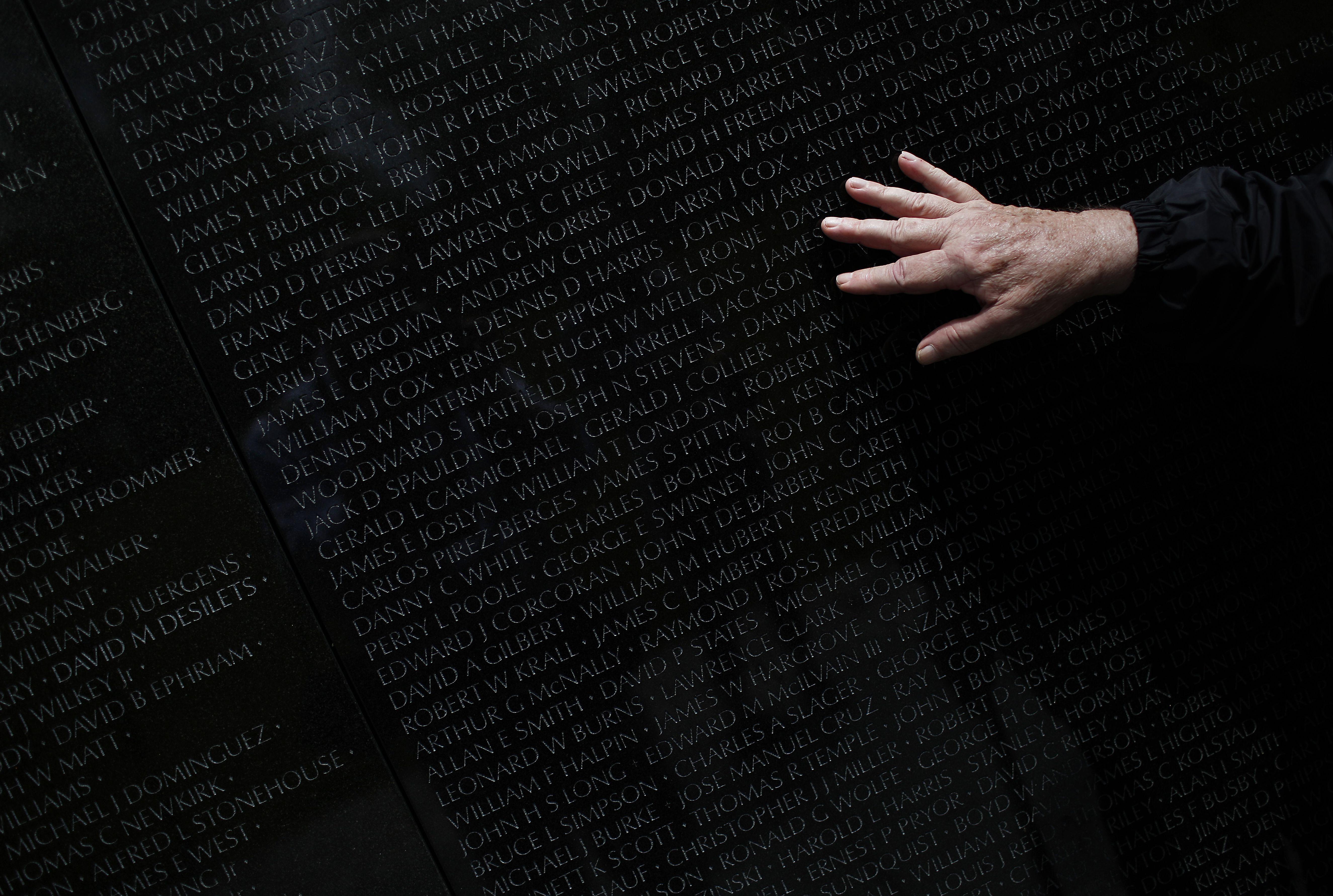 A hand touching the Vietnam War Memorial.