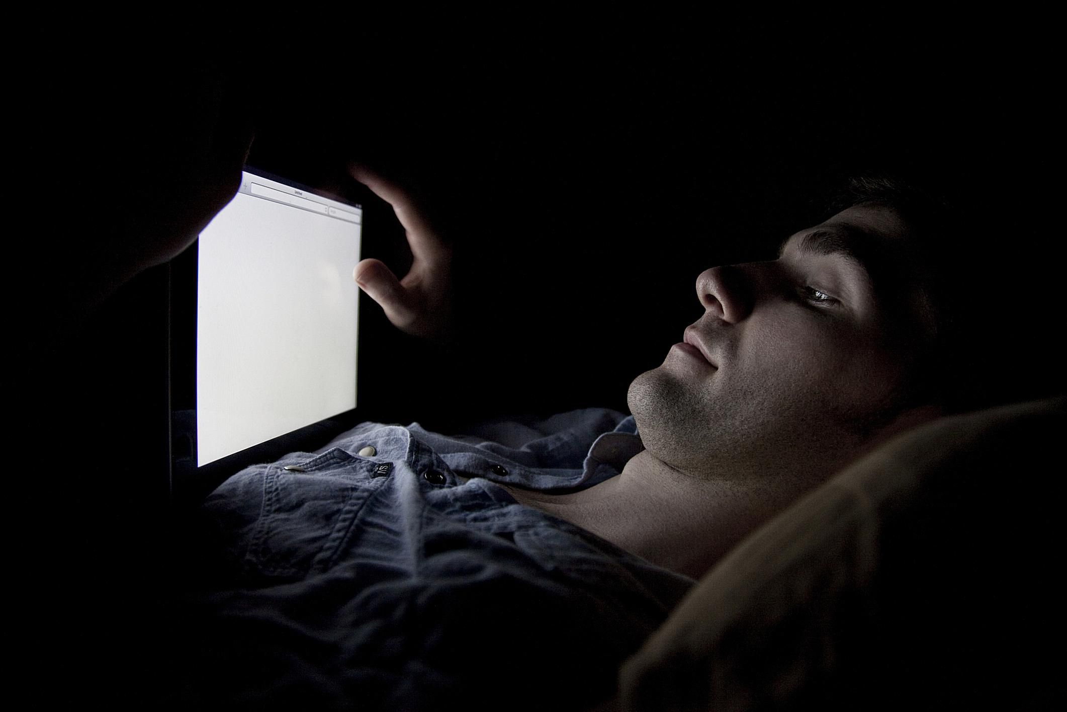 a man reading a tablet in the dark