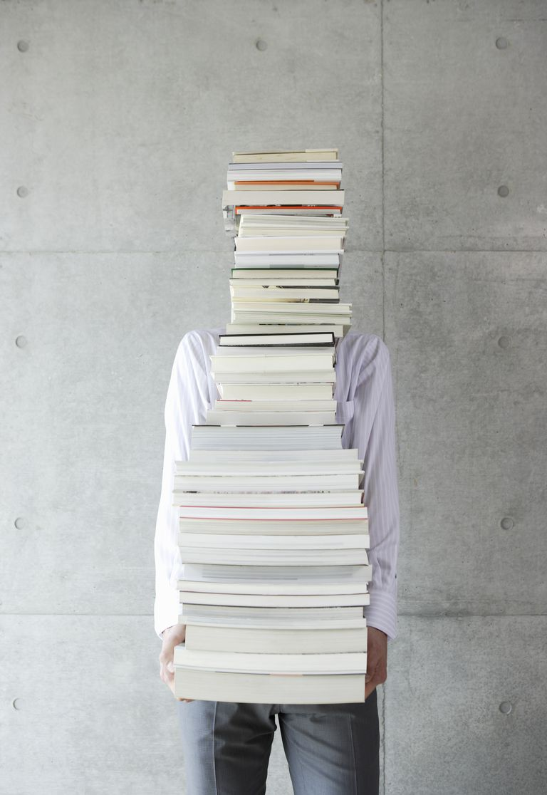 Young businessman holding a lot of books
