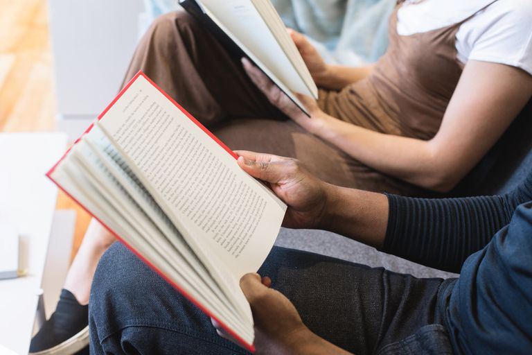 People sitting next to each other reading books