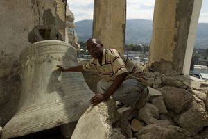 young black man sitting on rubble near a huge church bell that has fallen