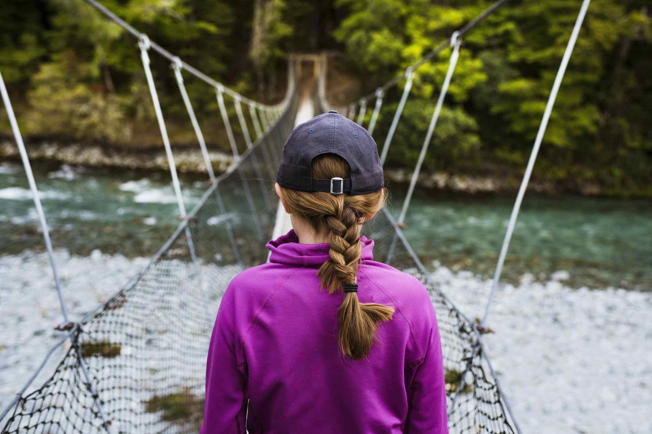 Girl crossing rope bridge