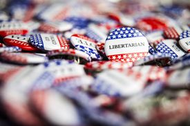 Close up of a pile of buttons for the Libertarian party.