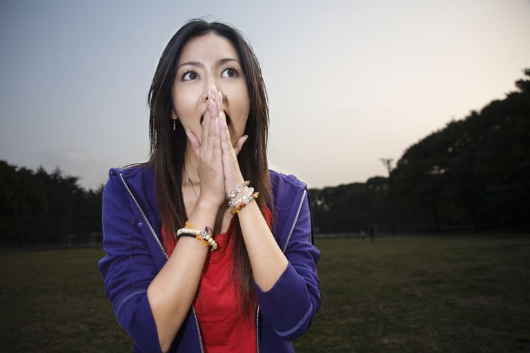 Young woman in park at dusk, hands covering mouth