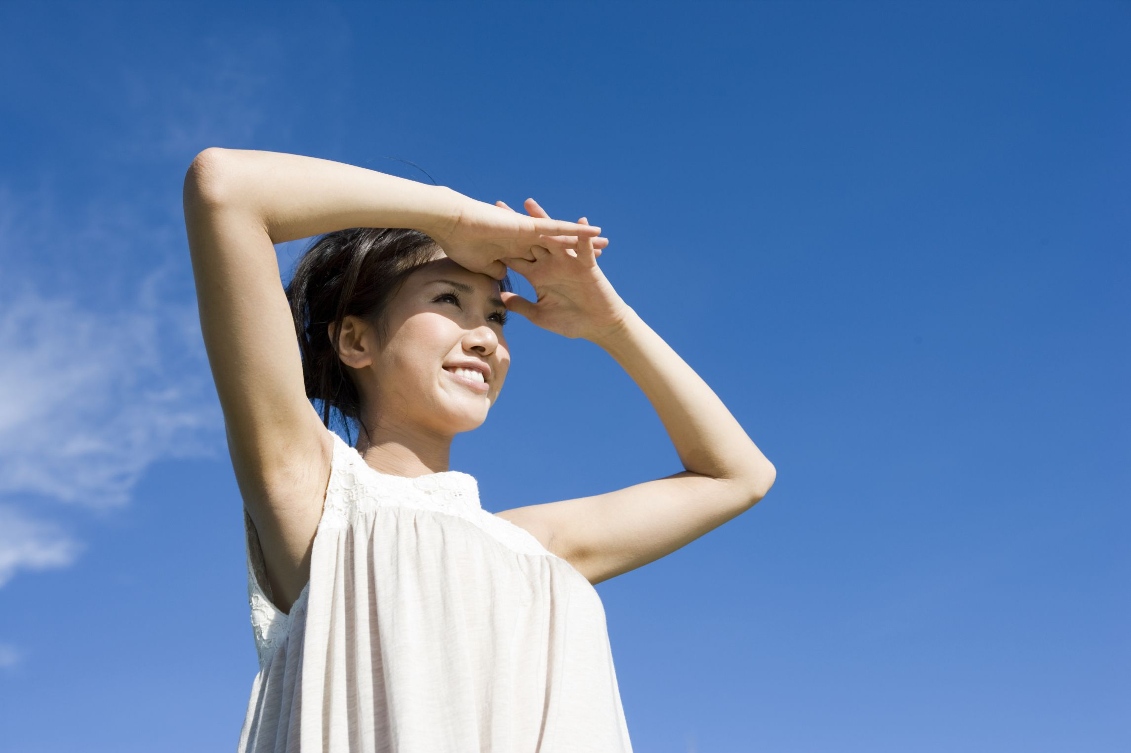 A woman shades her eyes from bright sunlight to see into the distance