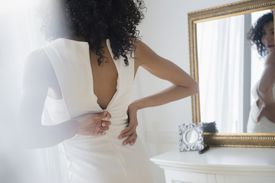 woman zipping up dress looking in mirror