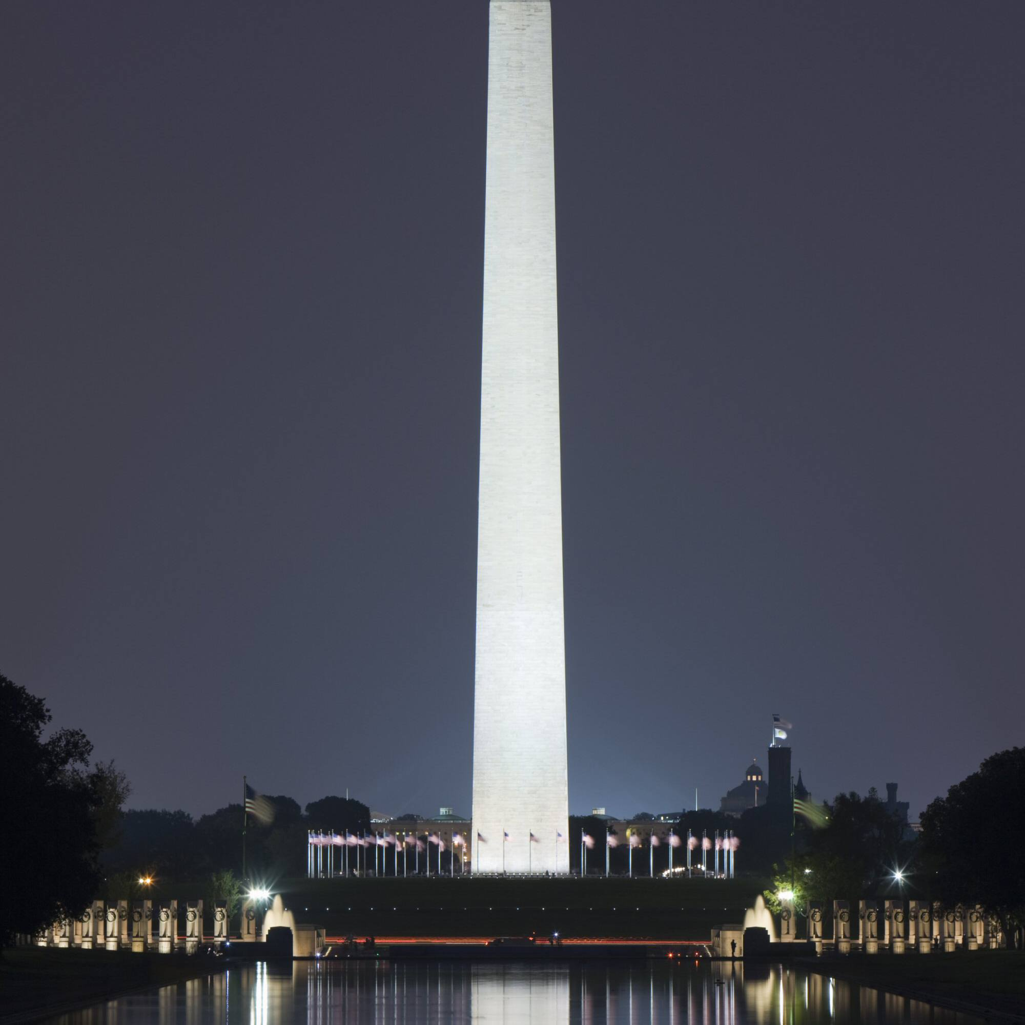 The Washington Monument illuminated at night, reflected in the Reflecting Pool