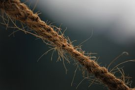 Close up of a rope fraying under the strain of being pulled