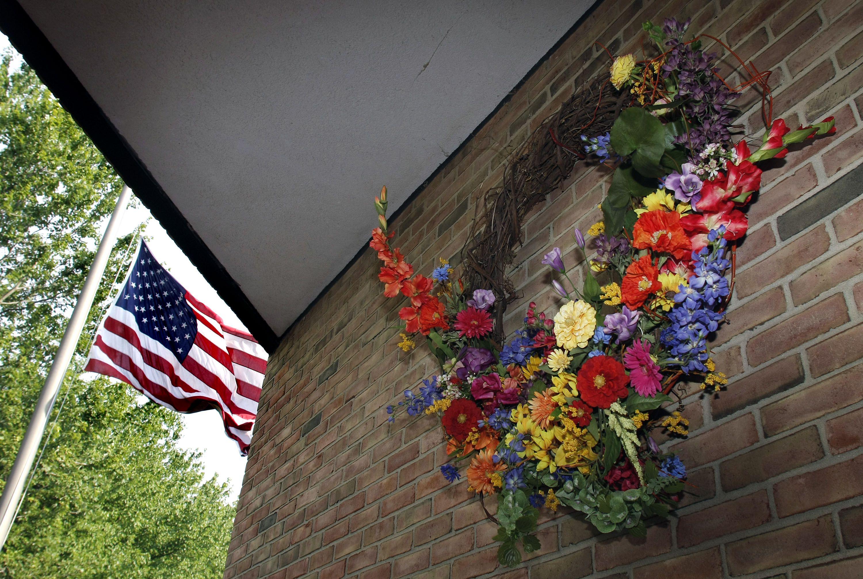 american flag near wreath on brick wall, detail of building