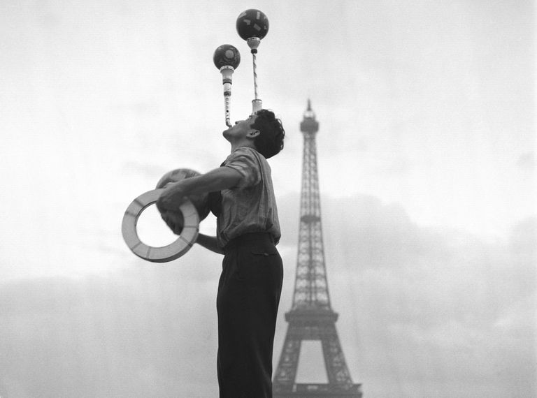 Man juggling in front of the Eiffel Tower in 1948