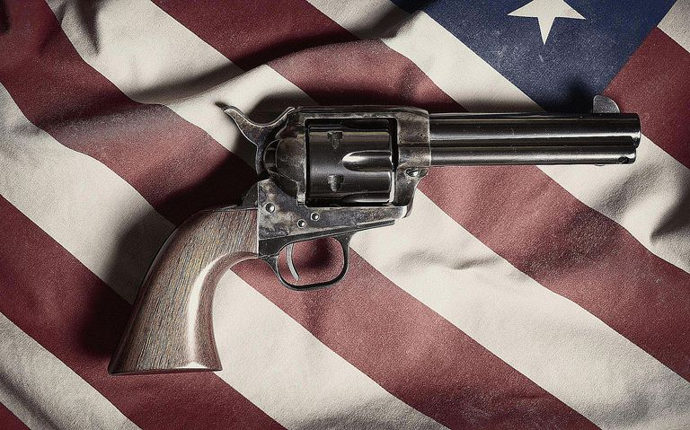 Colt Peacemaker set atop the American flag