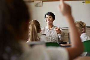 Teacher in class picking student with raised hand