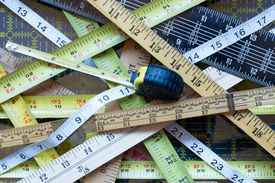 Random collection of Crisscrossed tape measures and yard sticks