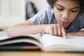 A boy reading a book at a desk