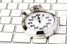 Image of a stopwatch on a computer keyboard.