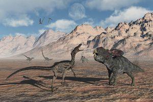 A predatory Velociraptor stalking a pair of Protoceratops.