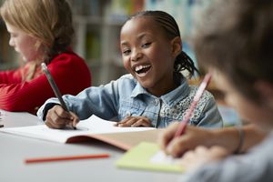 Child smiling and writing in booklet in classroom