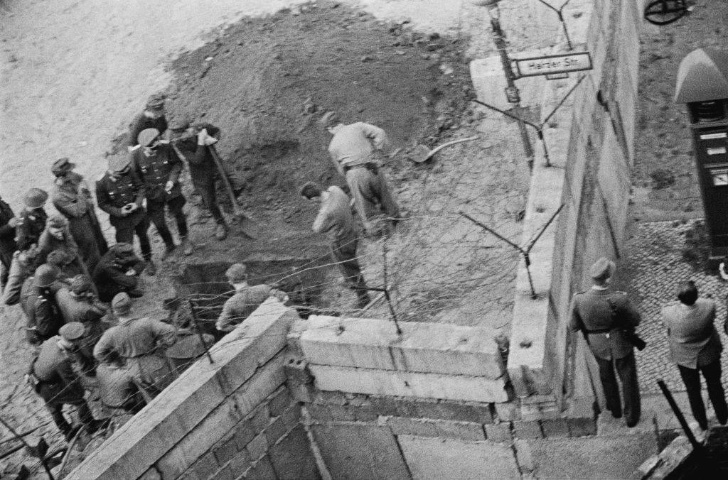 Group of East German soldiers investigate a tunnel dug beneath the Berlin wall.