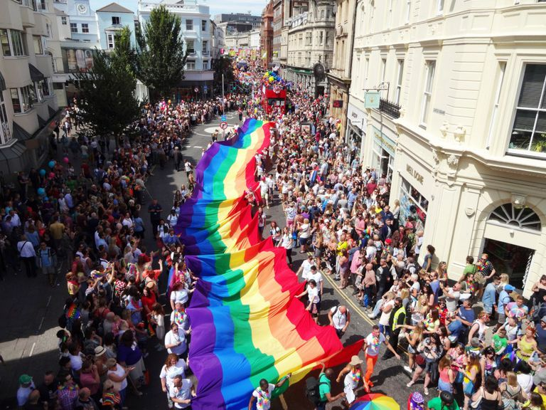 A large rainbow flag is carried in a Pride parade