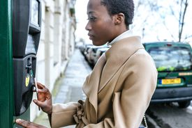 France, Paris, Young woman paying with her smartphone at parking automat