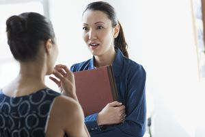 Two businesswomen gossiping in office hall