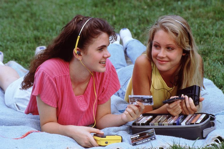 Two teenage girls listening to tapes in the neon eighties