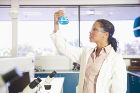 Mixed race scientist lifting beaker in laboratory