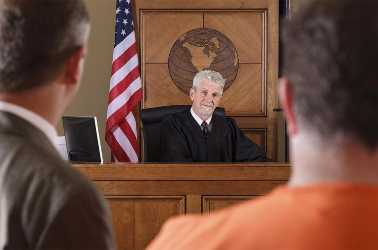 A judge as seen from behind the criminal defendant and his lawyer in a courtroom.