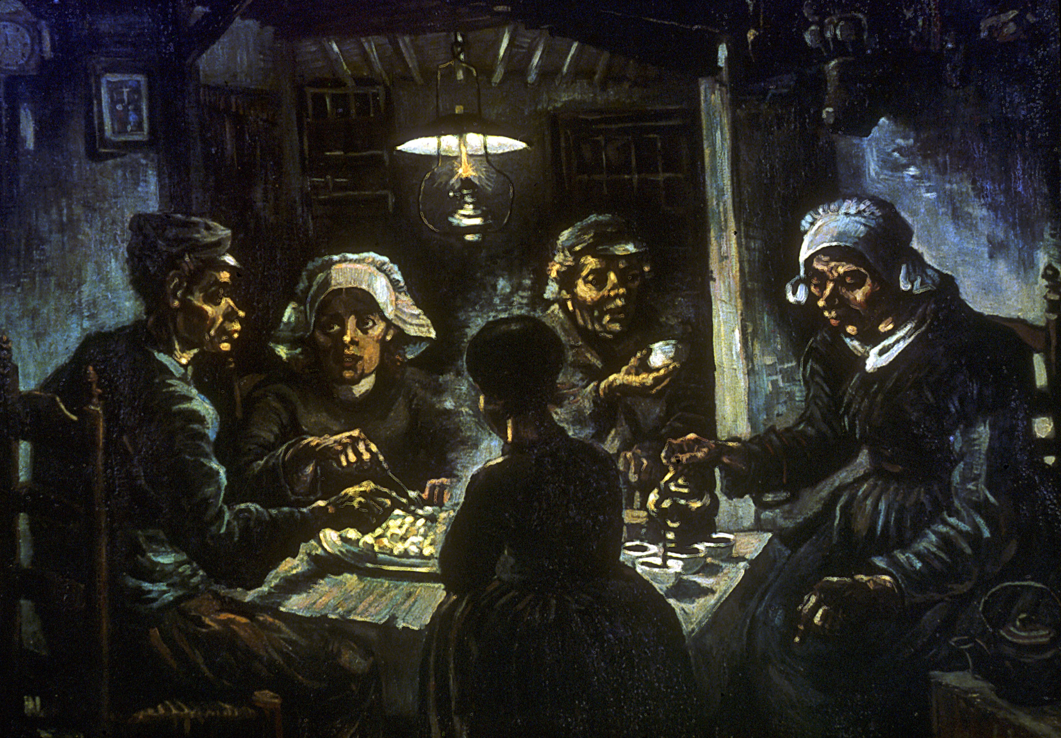 Five people huddle at a square table in a dark room illuminated by a single hanging lamp.