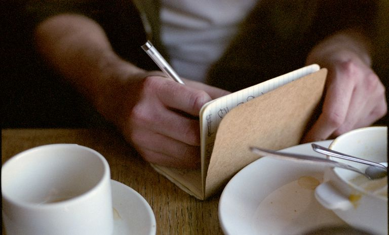 hands writing in notebook with empty teacup and plates