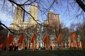 orange gates flutter in an urban park with tall, masonry city buildings in the background outside the park