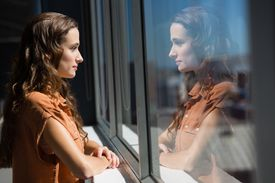Side view of thoughtful businesswoman looking through window