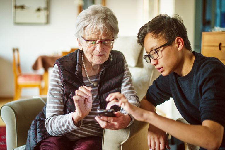 Teenage boy explaining mobile phone to senior woman