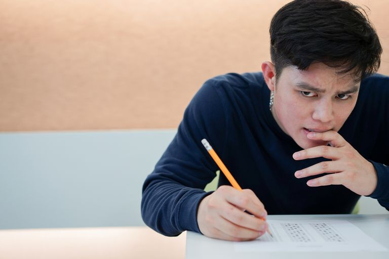 close up high school teenager student frowned and feeling stress and hard thinking after reading question about SAT test examination at classroom