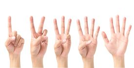 Close-Up Of Human Hand Counting Against White Background