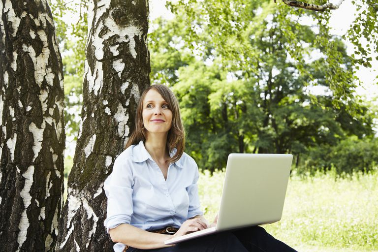woman sitting against tree with laptop editing the content on a website