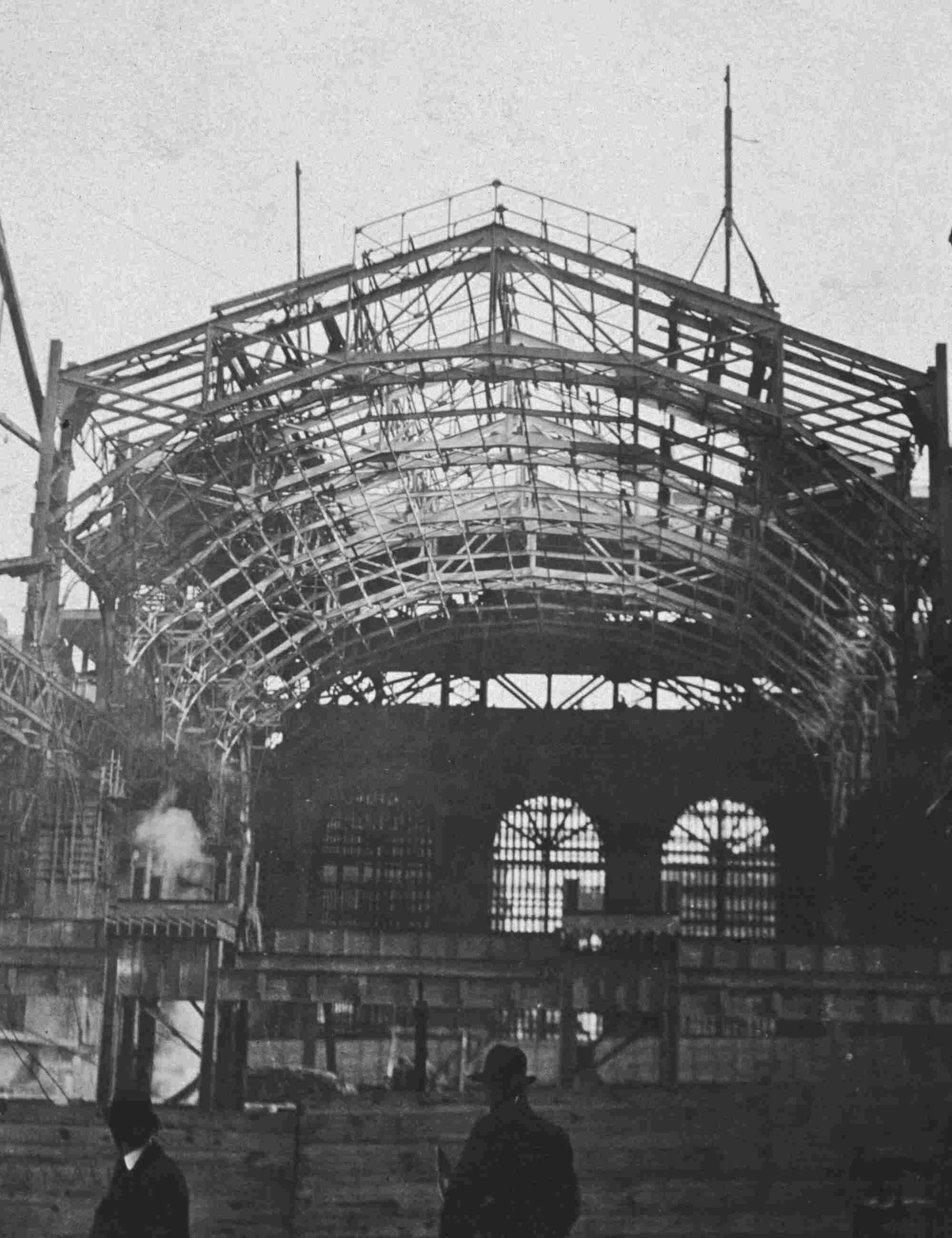 Archival photo 1907: Two men walk past metal framework of Grand Central Station during construction.