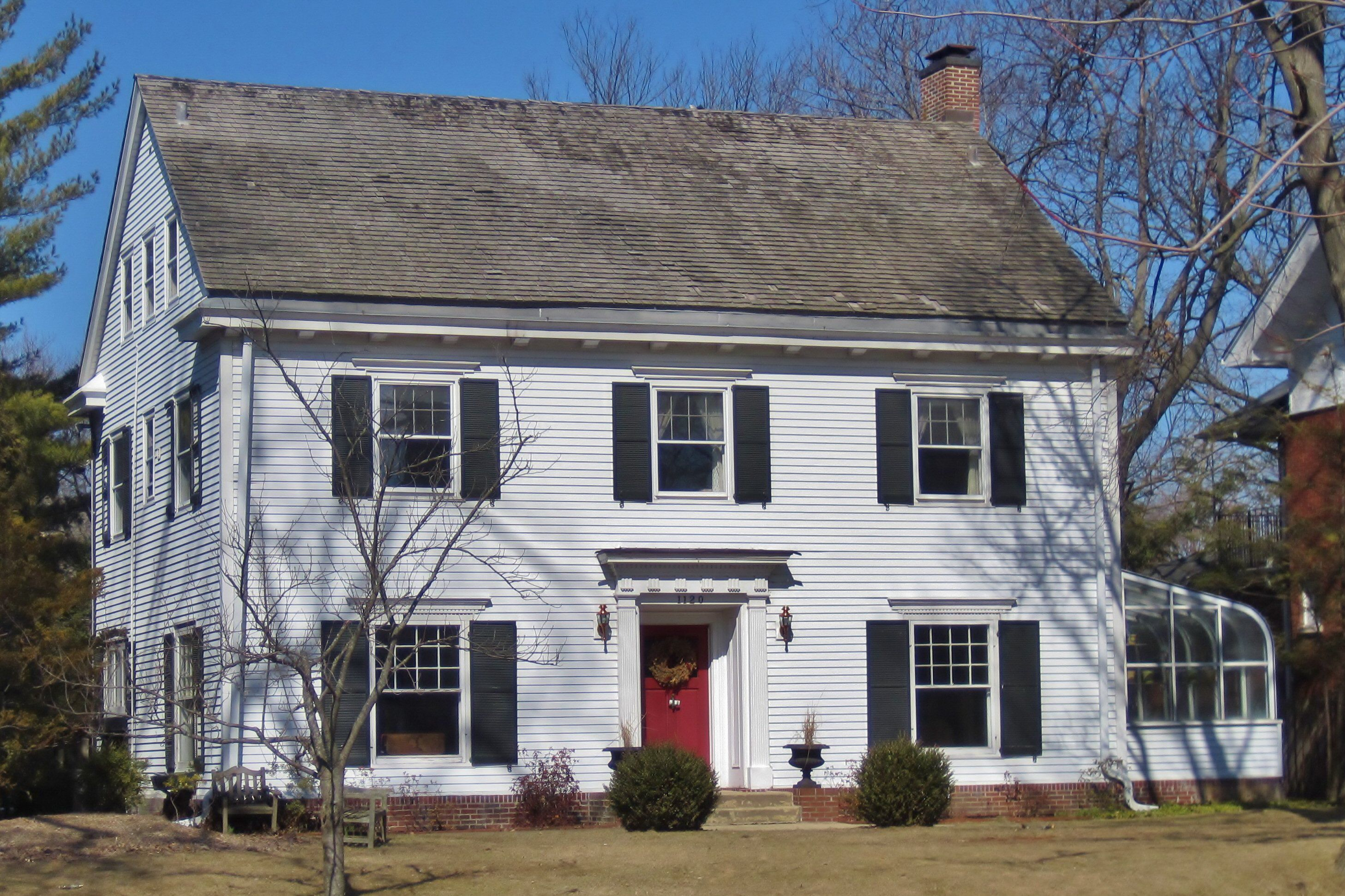 two story white house, 2 windows with black shutters on 2nd floor, 1 window on either side of red door