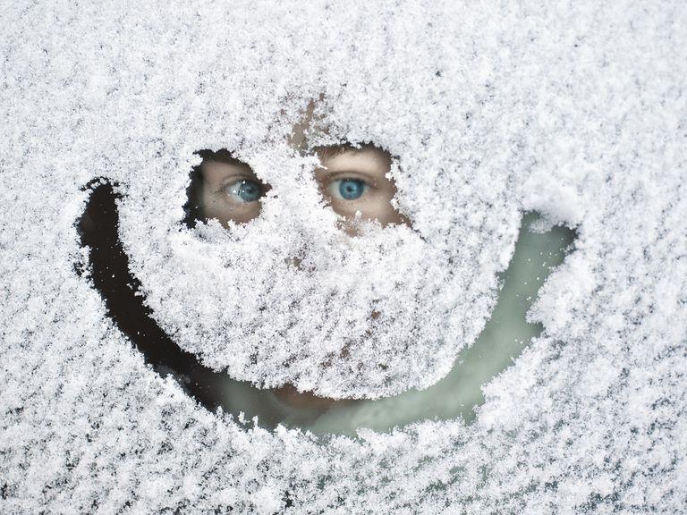 Man peeking through snow covered window