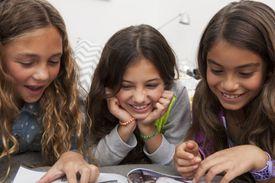 Three girls reading magazine