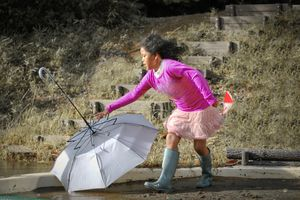 Girl with the umbrella in strong wind