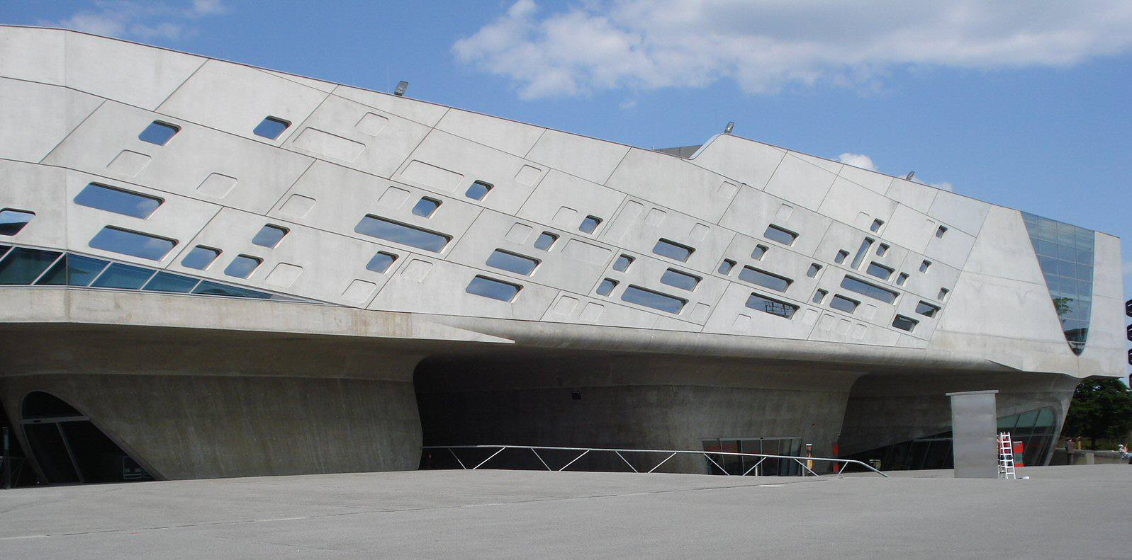 Horizontal concrete building with angled facing and square windows aligned with the facing.