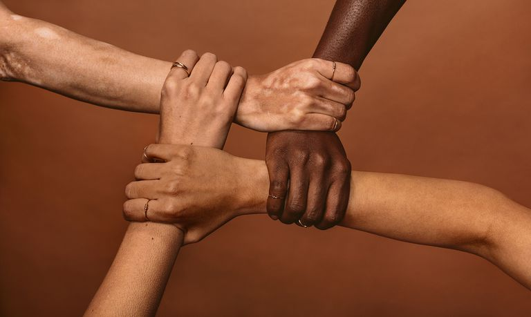 Four diverse women holding each other's wrists in a circle.