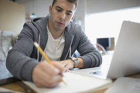 Business school applicant studying for exam with notebook and laptop