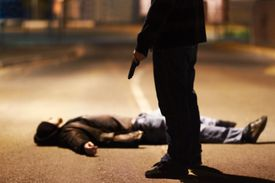 man lying dead on ground with man standing above him with gun