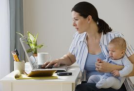 woman working on laptop with baby in her lap